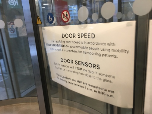 Sign on accessible over-sized revolving door